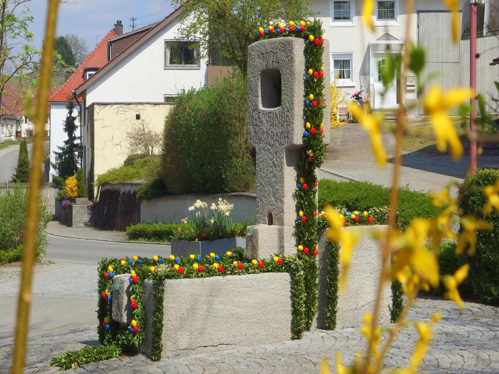 Geschmückter Dorfbrunnen in Marbach mit Kranz und bunten Ostereiern